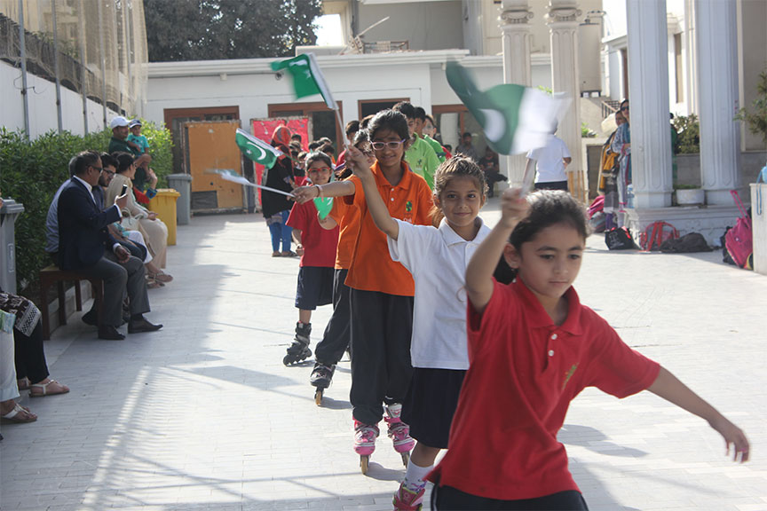 Students  roller skating as they wave a flag.